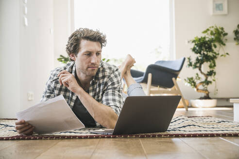Mid adult man lying on front using laptop at home - UUF21934