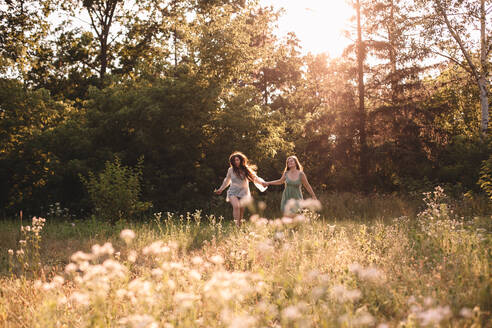 Happy lesbian couple holding hands while running in forest in summer - CAVF89833