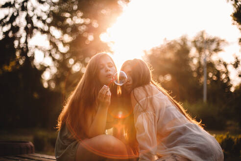 Lesbian couple blowing bubbles while sitting in park during summer - CAVF89839