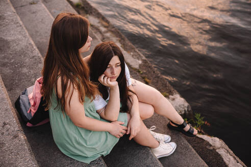 Girlfriends embracing while sitting on steps by river in city - CAVF89845
