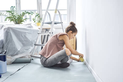 Young woman applying adhesive tape on wall while sitting at home - BSZF01720