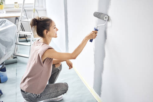 Smiling woman painting with paint roller on wall while crouching at home - BSZF01723