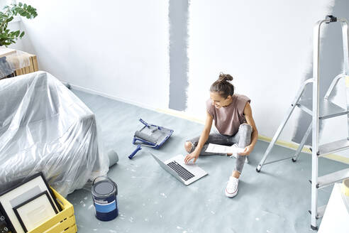 Woman with paper working on laptop while sitting at home - BSZF01735