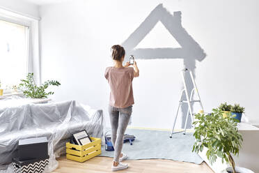 Young woman taking photo of house painted on wall through mobile phone while standing at home - BSZF01741