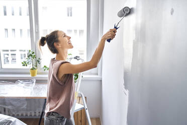 Smiling woman painting wall with paint roller while standing at home - BSZF01744