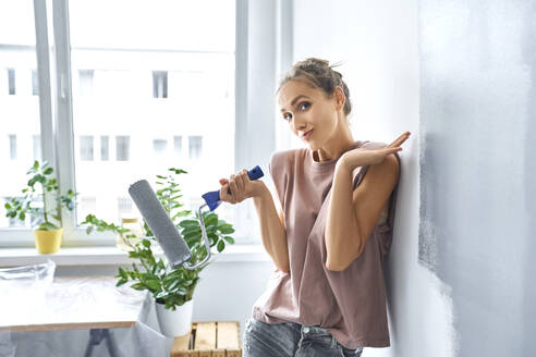 Beautiful young woman holding paint roller while leaning on wall at home - BSZF01747