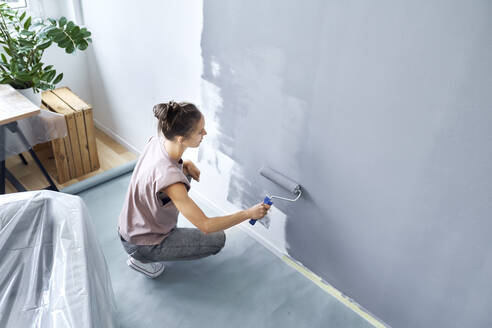 Young woman with paint roller painting wall while crouching at home - BSZF01750