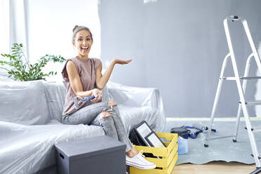 Happy woman holding paint roller while sitting on sofa at home - BSZF01753