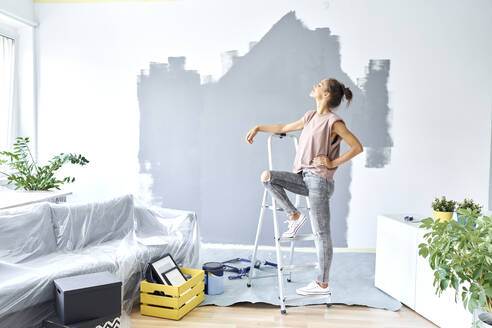 Woman with hand on hip leaning on ladder while standing against wall at home - BSZF01756