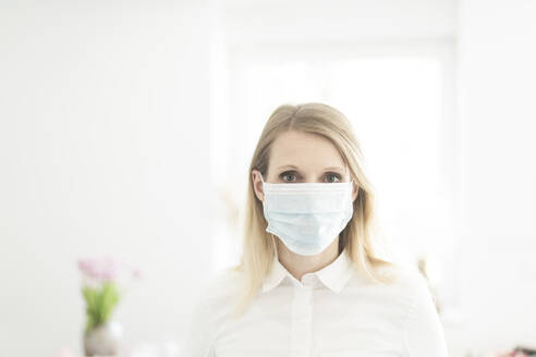 Blond woman wearing protective face mask while standing at office - CHPF00688
