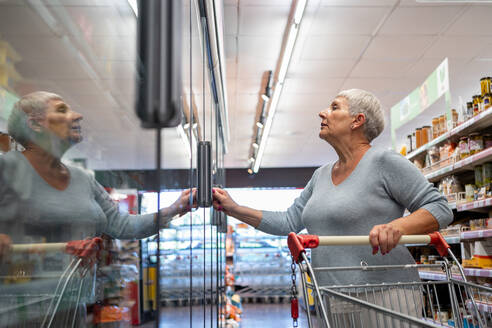 Caucasian elderly woman with white hair shopping in supermarket - CAVF89975