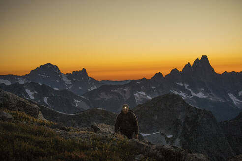 Hiker travels by headlamp on mountain ridge after sunet. - CAVF89996