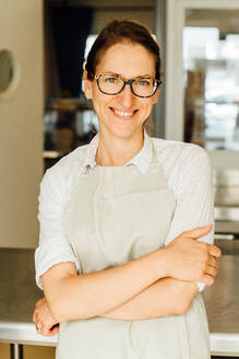 Portrait of female chef in glasses and apron smiling at camera - CAVF90005