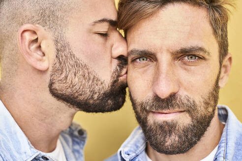Close-up of gay kissing man while standing against yellow wall - VEGF03042
