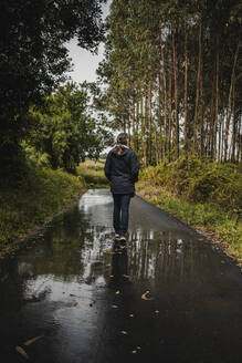 Rear view of woman walking on wet footpath during rainy season - DMGF00223