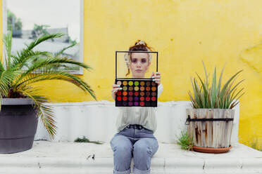Woman sitting with make up palette in back yard - MRRF00587