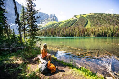 Hiker Sitting at Rawson Lake Looking Towards Sarrail Ridge in Rockies - CAVF90100