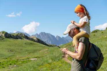 Father using smart phone while daughter sitting on his shoulder during sunny day - GEMF04294