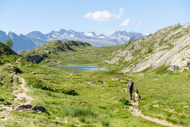 Father and daughter hiking in mountain during summer on sunny day - GEMF04297