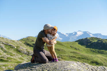 Father kissing daughter while kneeling on rock during sunny day - GEMF04306