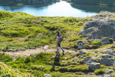 Mother hiking in mountain with daughters on sunny day during summer - GEMF04309