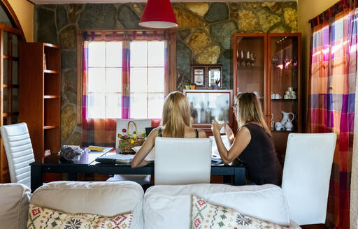 Mother sitting with daughter at dining table while studying in living room - MGOF04597