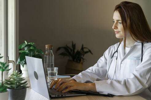 Young female doctor using laptop during online consultation at home office - AFVF07376