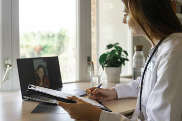 Young female doctor discussing with patient during online consultation - AFVF07382