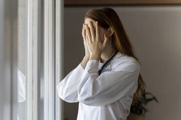 Emotionally stressed young female doctor with head in hands standing by window - AFVF07385