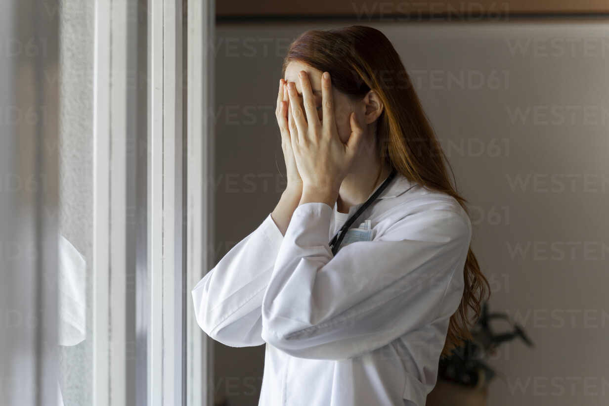 Emotionally stressed young female doctor with head in hands standing by window - AFVF07385 - VITTA GALLERY/Westend61