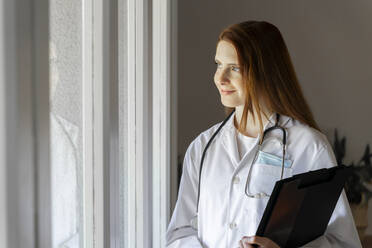 Thoughtful young female doctor smiling while looking through window in home office - AFVF07391