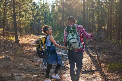 Happy young couple with backpacks hiking in sunny woods - CAIF29830