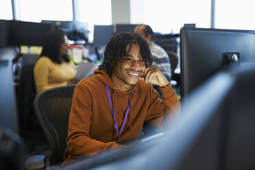 Smiling businessman working at computer in office - CAIF29965
