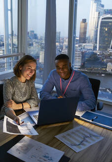 Business people working at laptop in highrise office, London, UK - CAIF29971