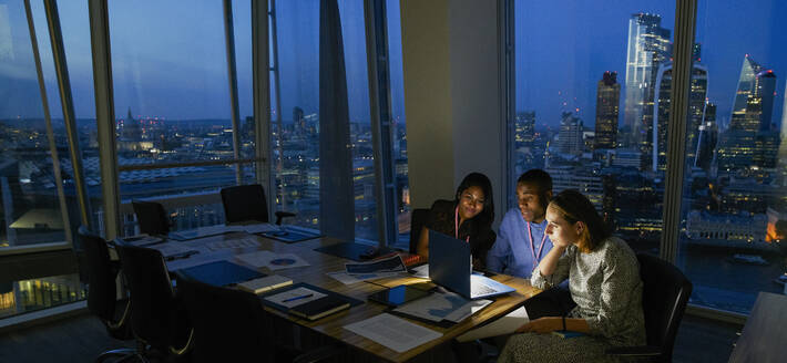 Business people working late at laptop in highrise office, London, UK - CAIF29974