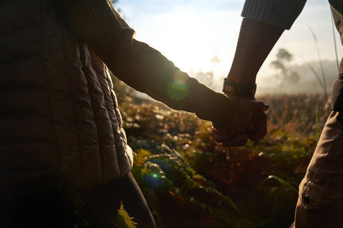Close up silhouette young couple holding hands on sunny hike in nature - CAIF30007