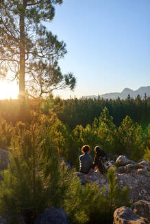 Young hiker couple enjoying sunny view of trees in woods at sunset - CAIF30019