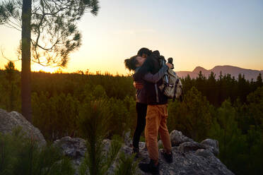 Affectionate young hiker couple hiking on rock in sunset woods - CAIF30067
