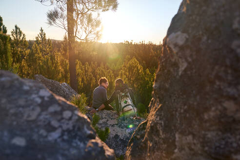 Affectionate young hiker couple relaxing on rock in sunny sunset woods - CAIF30070