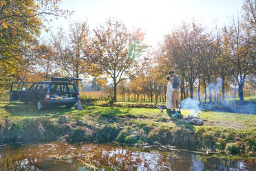 Affectionate young couple camping in sunny autumn field - CAIF30073