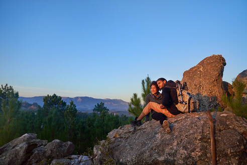 Young hiker couple relaxing on rock and enjoying sunset - CAIF30076