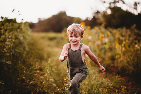 Smiling boy running in a field with sunflowers in the background - CAVF90173