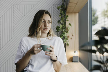Young woman holding coffee cup looking through window while standing in cafe - LHPF01309