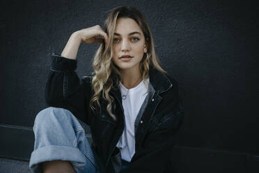 Beautiful woman with hand in hair sitting against wall - LHPF01330