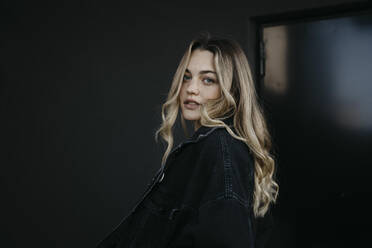 Young woman wearing denim jacket while standing against black wall - LHPF01342