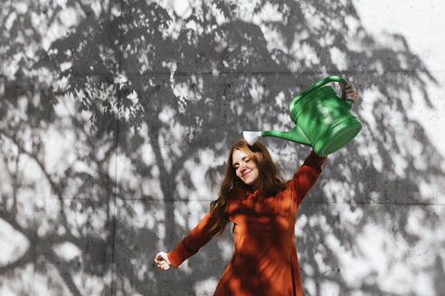 Woman holding watering can up while standing against tree shadow wall - TCEF01217