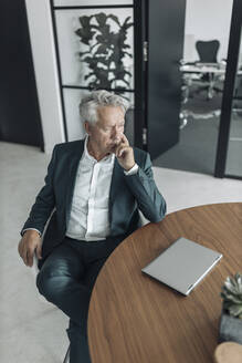 Thoughtful businessman sitting on chair by table at office - GUSF04476