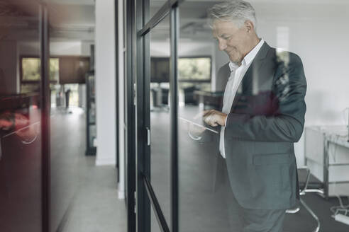 Smiling businessman using digital tablet while standing by glass wall at office - GUSF04479