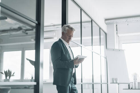 Businessman using digital tablet while standing by glass wall at office - GUSF04521