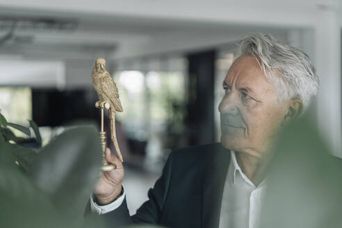 Businessman holding artificial pigeon model while standing at office - GUSF04527